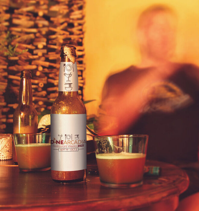 Beer bottle and glass on table with blurred man in background