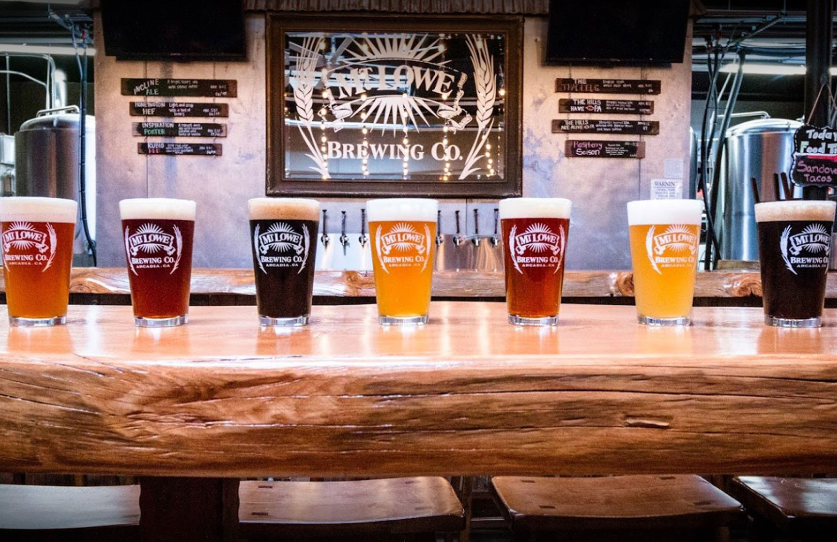 Different flavors of beer in glasses on a bar.